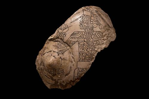 Engraved shell of figure with tattoos and earspools